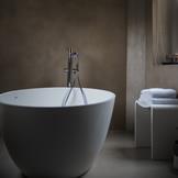 Évier dans une salle de bain avec un mur béton ciré