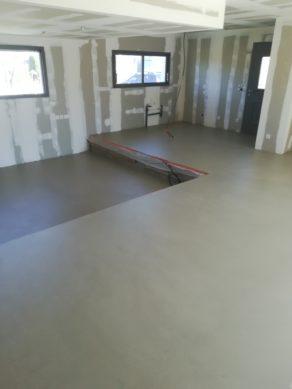 elégant sol d'un salon en béton ciré vernis mat couleur grège dans le gard pour un particulier
