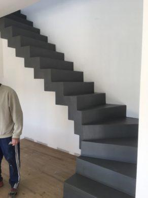 splendide escalier crémaillère dans une pièce à vivre en béton ciré couleur alchimie aureville  pour un maitre d'œuvre
