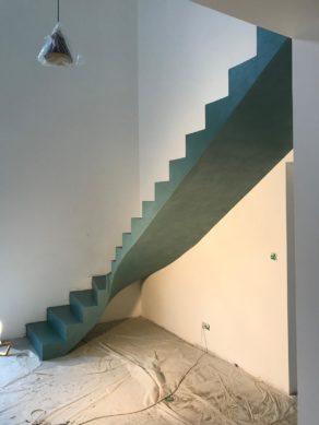 audacieux  escalier crémaillère dans une pièce à vivre en béton ciré vernis mat couleur malachite  pour un particulier