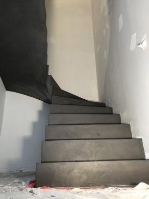 superbe escalier à paillasse deux quart tournant en béton ciré couleur gris orbital  pour un constructeur