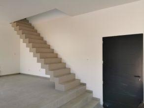 sublime escalier crémaillère dans une pièce à vivre en béton ciré vernis mat couleur galet original À arcachon proche Bordeaux  pour un architecte