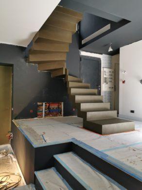audacieux  escalier crémaillère deux quart tournant en béton ciré vernis mat couleur gibraltar Au Pyla-Sur-Mer en Aquitaine dans le sud ouest de la France.  pour un maitre d'œuvre