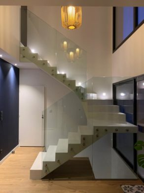 Escalier avec paliers intermédiaires en beton ciré et garde corps en verre