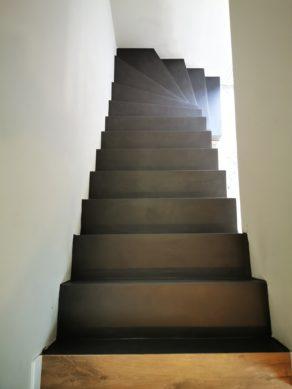 Arrivée d'une volée de marches d'escalier habillée en béton ciré