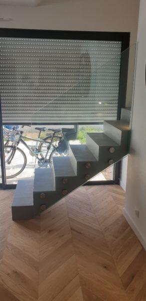 Départ d'un escalier béton protégé par un garde corps en verre sur plots