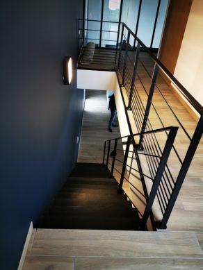 Descente d'un escalier en béton ciré avec garde corps en fer forgé noir