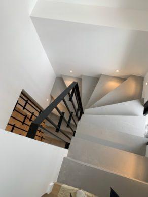 Béton ciré gris clair fossile sur cet escalier éclairé avec des lumières incrustées dans les murs et un garde corps sur mesure