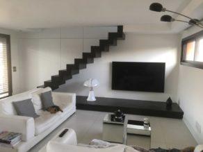 Estrade sous l'escalier avec un effet flottant décoré en béton ciré de la même couleur que l'escalier