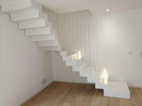 Application d'un béton ciré blanc pur sur un escalier béton un quart balancé avec une première marche palière