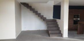 Application d'un béton ciré couleur Nubuck sur un escalier sur fond d'un mur blanc