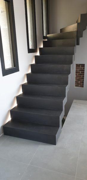 Application d'un béton ciré gris anthracite sur un escalier moderne décollé du mur